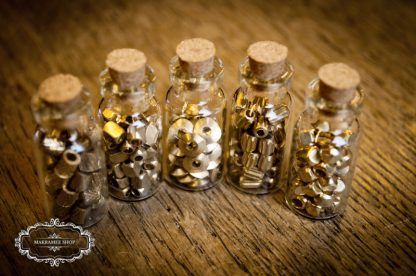 Messingperlen in Glasfläschchen